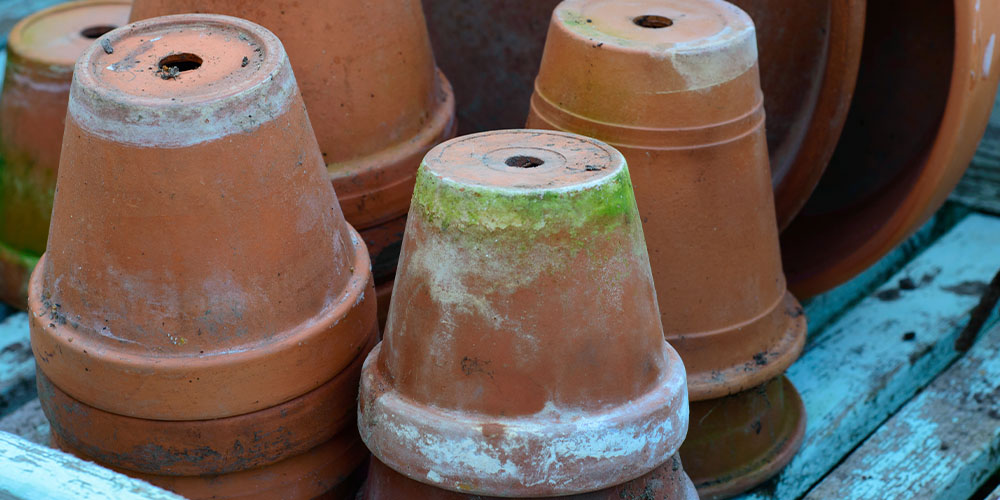 terra cotta pots with white minteral deposits