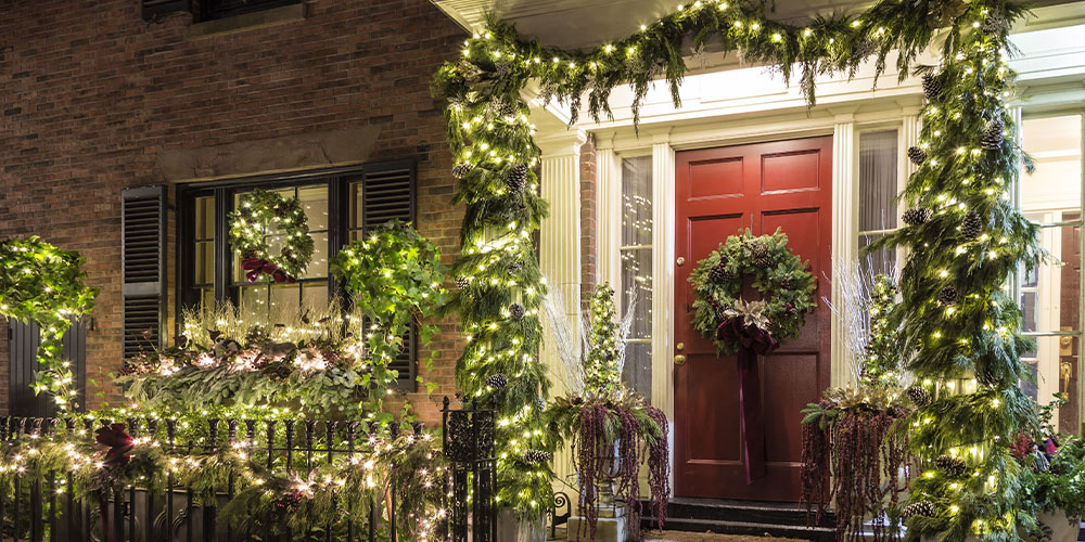 gorgeous lit up Christmas exterior with greens