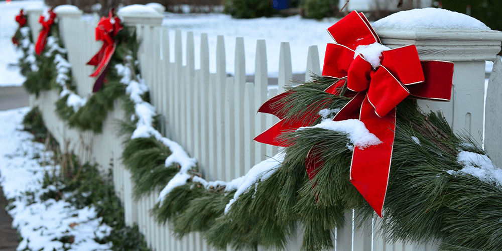 evergreen garland on white fence